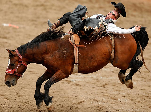 Wes Stevenson loses his hat while riding Hurricane Terry in the bareback event of the 100th anniversary of the Calgary Stampede Rodeo on July 13.