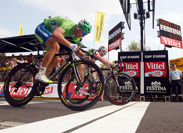 Andre Greipel of Germany narrowly crosses the finish line ahead of Peter Sagan of Slovakia, wearing the best sprinter's green jersey, to win stage 13 of the Tour de France.  After the racers traveled 134.8 miles over the course of almost five hours, the two men were separated by less than a second.