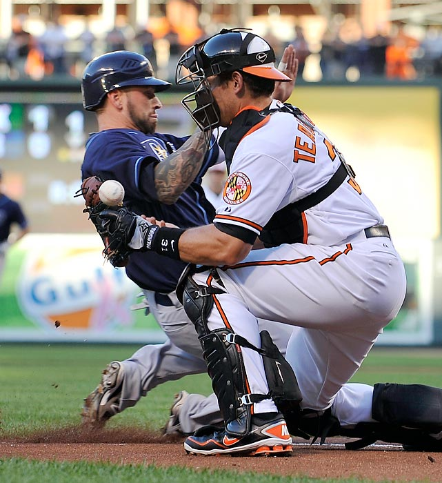 Baltimore Orioles catcher Taylor Teagarden can't hold on to the ball as Tampa Bay Rays' Ryan Roberts slides safely into home during the first inning.  The Rays went on to rout the Orioles 10-1.