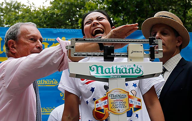 "Sonya (The Black Widow) Thomas stands on a scale as she's weighed by New York City Mayor Michael Bloomberg (L) during the official ""weigh-in"" FOR THE annual Nathan's Famous Coney Island 4th of July Hot Dog-Eating Contest. The photo was shot at New York's City Hall Park on July 3."