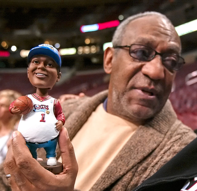 "Bill Cosby holds a ""Fat Albert"" bobblehead doll before the start of a 2004 76ers-Bucks game in Philadelphia."