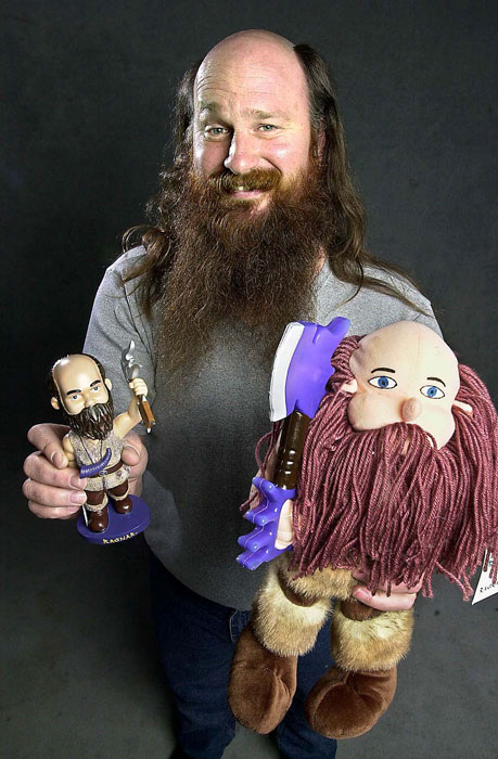 Minnesota Vikings mascot Ragnar holds up his bobblehead and rag doll.