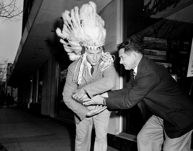 University of Miami fullback Don Bosseler was drafted in the first round by the Redskins and is pictured here with a feathered headdress as he gets the traditional rookie initiation with Coach Joe Kuharich.