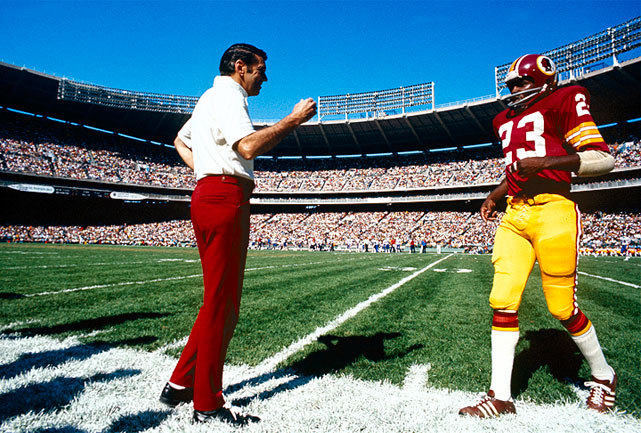Redskins coach George Allen waits to congratulate Charlie Taylor as he comes off the field to catch his breath.  Allen had taken the team to the Super Bowl three seasons earlier, which resulted in a loss to the Miami Dolphins.