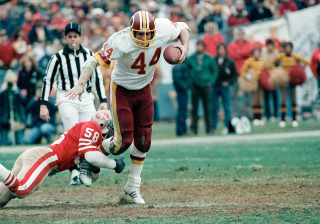 John Riggins (44) breaks a tackle against the San Francisco 49ers.  During the '83 season Riggins rushed for 1,347 yards, and then-NFL record 24 touchdowns, and was named an All-Pro for the first time in his career.