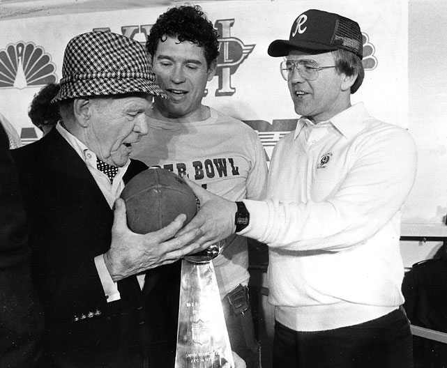 Washington Redskins owner Jack Kent Cooke, left, running back John Riggins, and head coach Joe Gibbs, right, share the game ball in the locker room after a Super Bowl XVII win over the Dolphins.  Riggins was named the MVP of the game after scoring a go-ahead touchdown in the fourth quarter.