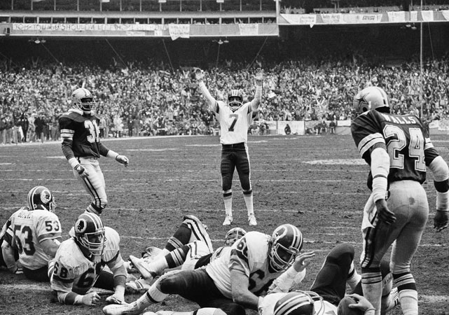 Quarterback Joe Theismann (7) celebrates after John Riggins score their second touchdown against division rival Dallas Cowboys at RFK Stadium in Washington.  Riggins would later be inducted into the Hall of Fame in 1992.