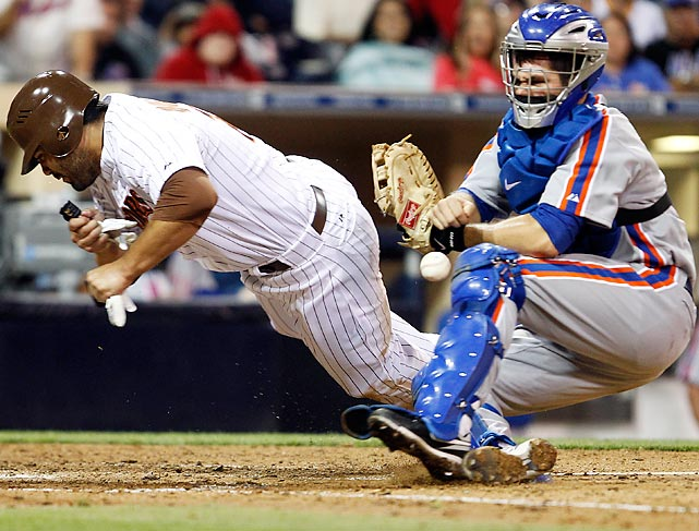 Carlos Quentin of the San Diego Padres separates the ball from New York Mets catcher Josh Thole during a  6-2 loss.