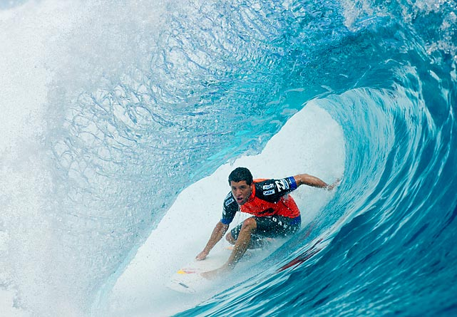 Adriano De Souza of Brazil surfs the tube during his first-round heat at the Billabong Pro Tahiti in Teahupoo.