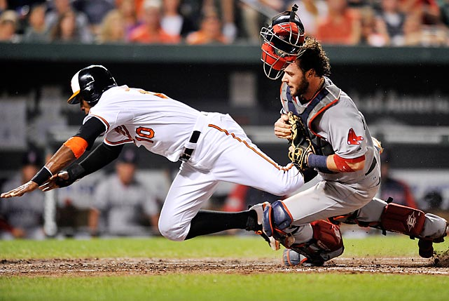 Adam Jones of the Orioles is called out after colliding with Boston catcher Jarrod Saltalamacchia.