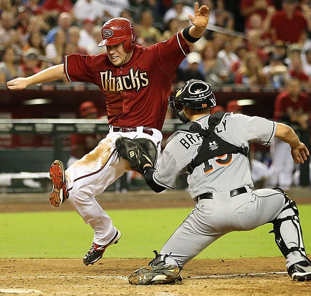 Miami catcher Rob Brantly tags out Arizona's Aaron Hill despite some acrobatics from the Diamondbacks second baseman in the ninth inning. The Diamondbacks won 3-2.