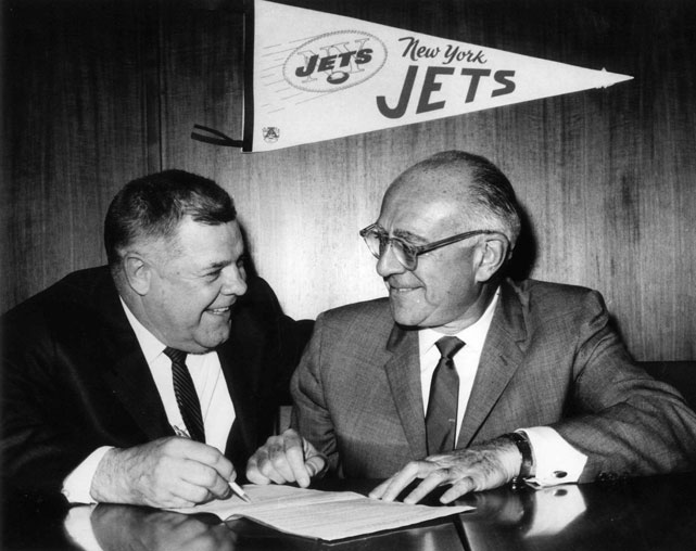Weeb Ewbank (left) signs a contract with owner Sonny Weblin, retaining him as the head coach and general manager of the Jets.