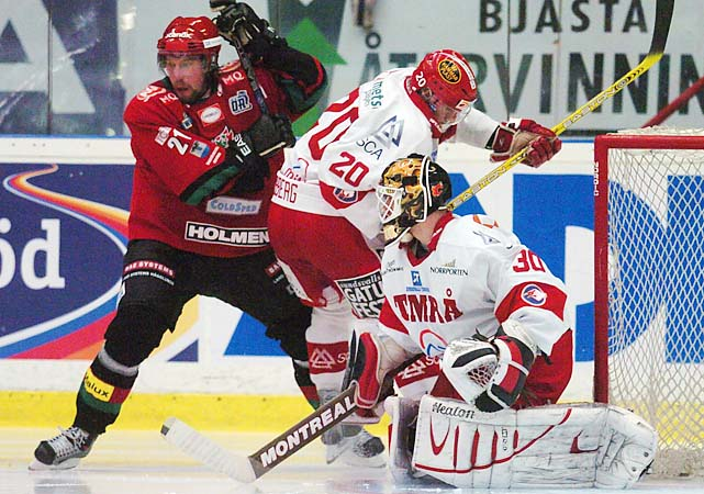 Peter Forsberg, left, fights it out with Henrik Zetterberg in front of goalie Miika Kiprusoff during a Swedish national league match between Modo and Timra in Ornskoldsvik, northern Sweden on Sept. 27, 2004.