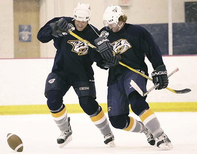 Predators Jim McKenzie, left, and Scott Hartnell chase a football on the ice at the end of a workout at the team's practice facility on Sept. 15, 2004, the last day players were able to use team facilities before the league locked out the players.