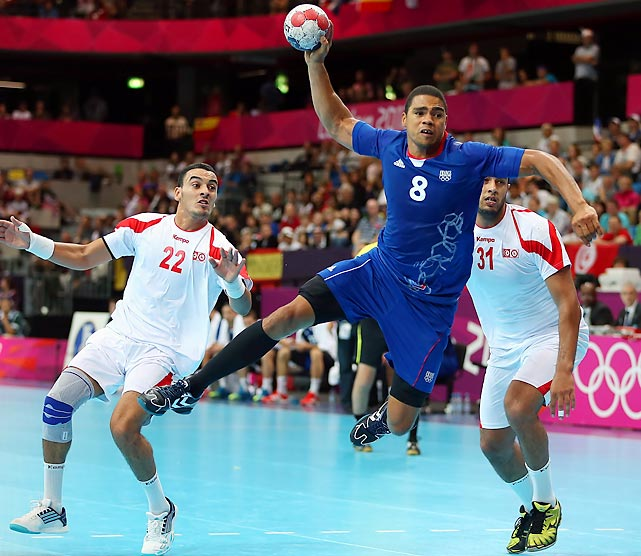 France's Daniel Narcisse (8) takes a shot, which scored, against Oussama Boughanmi (22) and Marouan Chouiref (31) of the Republic of Tunisia on Thursday during the preliminary stage of the men's handball competition at the Olympic Games in London. France defeated the North African nation 25-19 to stay undefeated through six matches in group play.