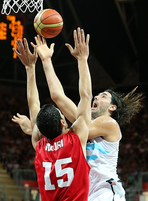 "Argentinean forward Luis Scola, of the NBA's Phoenix Suns, goes up for a shot over the Republic of Tunisia's Salah Mejri (15) in the first half of a preliminary round game on Thursday at London's ""Marshmallow"" Basketball Arena. Although Tunisia -- the only team in the Olympic basketball tournament without an NBA player on its roster -- gave Argentina a scare after building a 14-point lead following the first quarter, the South Americans were paced by Manu Ginobili's 24 points, eventually winning 92-69."