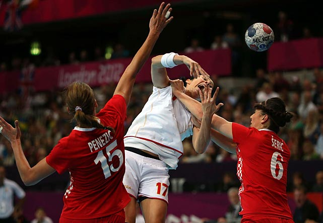 Bojana Popovic (17) of Montenegro got the ball off despite the strong-arm tactics of Croatia's Andrea Seric (6) and Andrea Penezic in their Group A preliminary match, won 27-26 by Croatia.