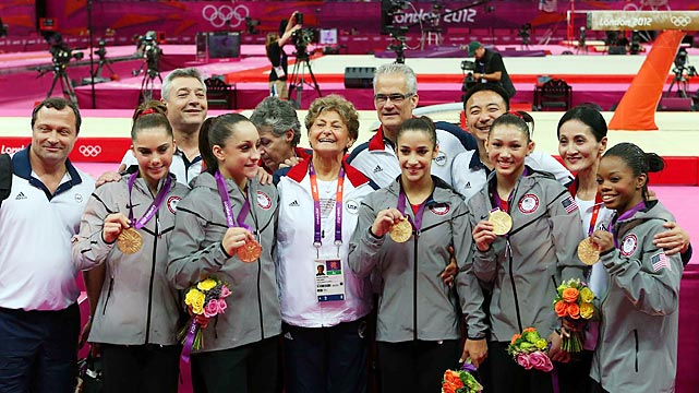 Gabby Douglas (far right) poses with her teammates and coaches after Team USA took gold in the Olympic all-around team final.