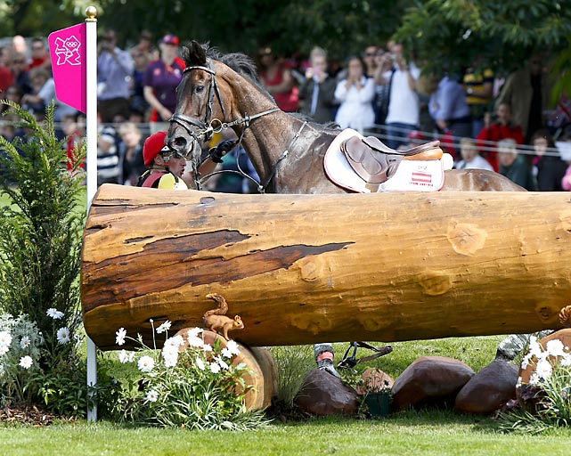 Harald Ambros of Australia falls off before a jump in the Equestrian event.