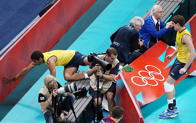 Brazil's Wallace de Souza crashes right over a photographers section in the men's volleyball quarterfinal against Argentina.