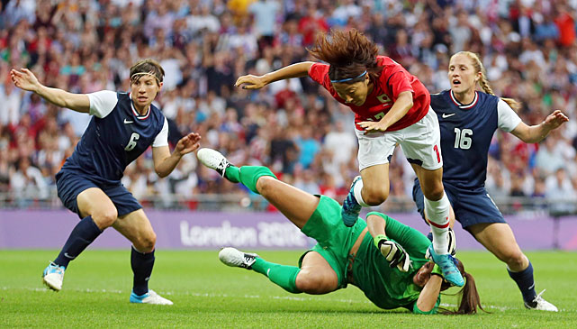 Yuki Ogimi of Japan goes flying over U.S. goalkeeper Hope Solo in an unsuccessful scoring attempt.