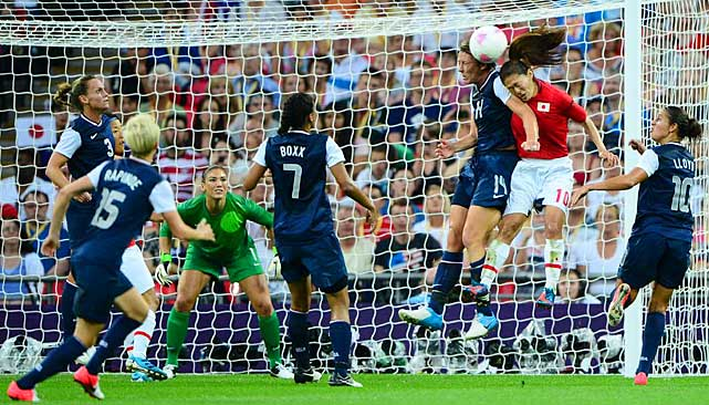 Abby Wambach goes up to defend against a scoring attempt by Japan.