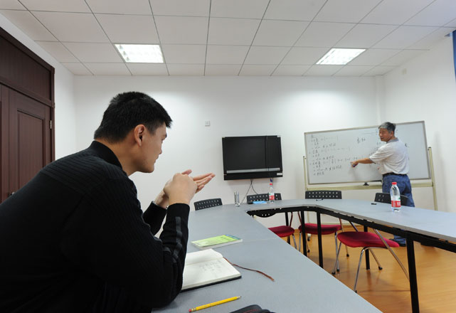 Yao listens to his teacher on the first day as a new student of the Antai College of Economics & Management at Shanghai Jiao Tong University. He is mostly taking one-on-one lectures to avoid attention while on campus.