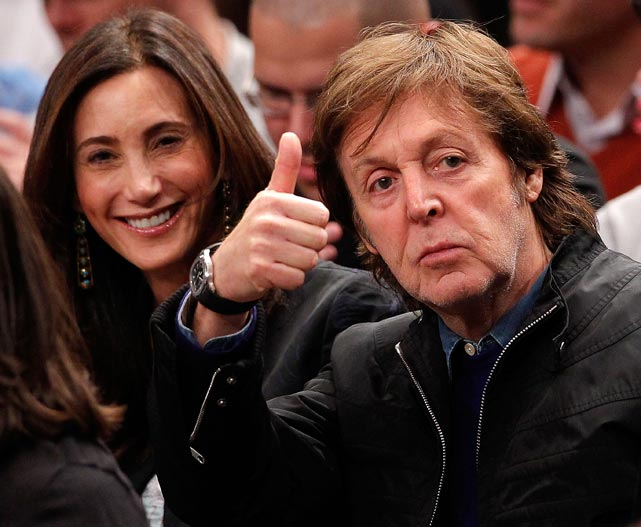 Former Beatle Paul McCartney gives a thumbs up to fans as wife Nancy Shevell smiles during a New Orleans Hornets-New York Knicks game.
