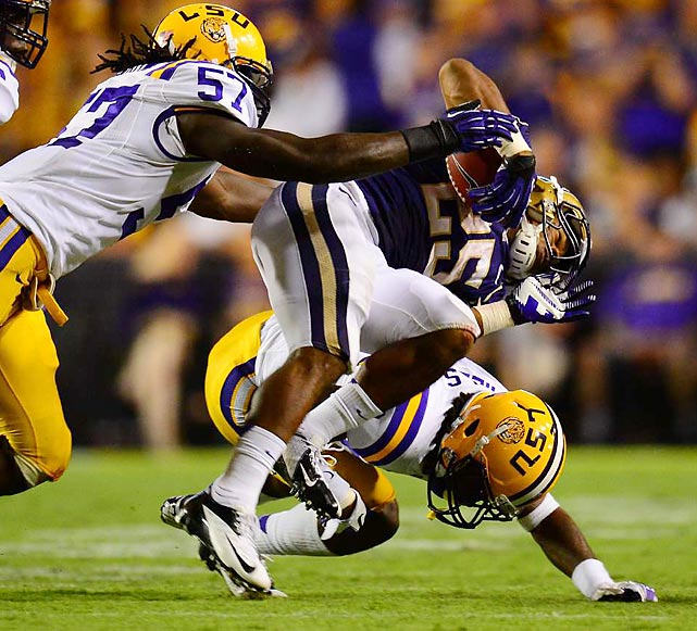 Washington's Bishop Sankey is upended by two LSU defenders, one of many hard hits the Huskies took all night. LSU throttled Washington 41-3 at Tiger Stadium in Baton Rouge.