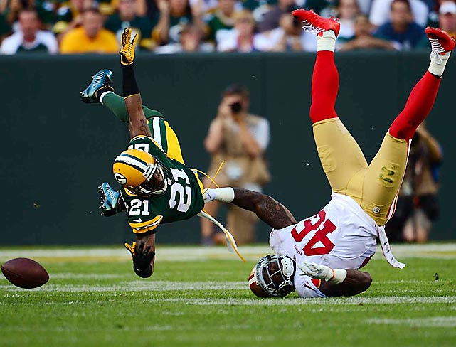 Charles Woodson showcases his acrobatic abilities after flying in to break up this pass intended for 49er tight end Delanie Walker.
