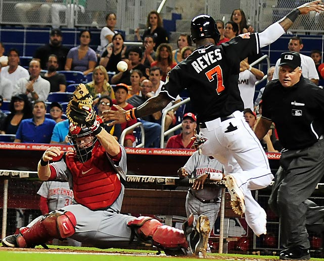 The Marlins' Jose Reyes dodges Reds' catcher Ryan Hanigan, who can't haul in the ball during a game at Marlins Park.