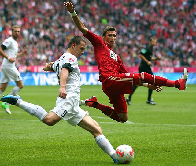 Bayern Munich's Mario Mandzukic is challenged by Zdenek Pospech of Mainz during a game in Munich.