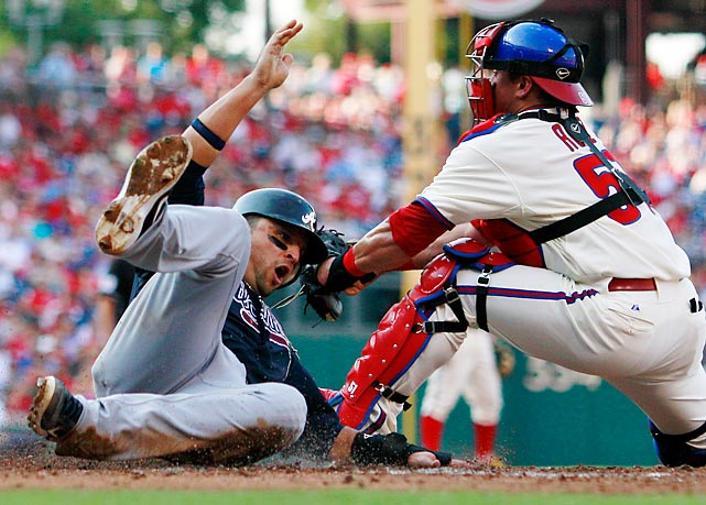 Atlanta Braves' Martin Prado scores past the tag of Philadelphia's Carlos Ruiz.