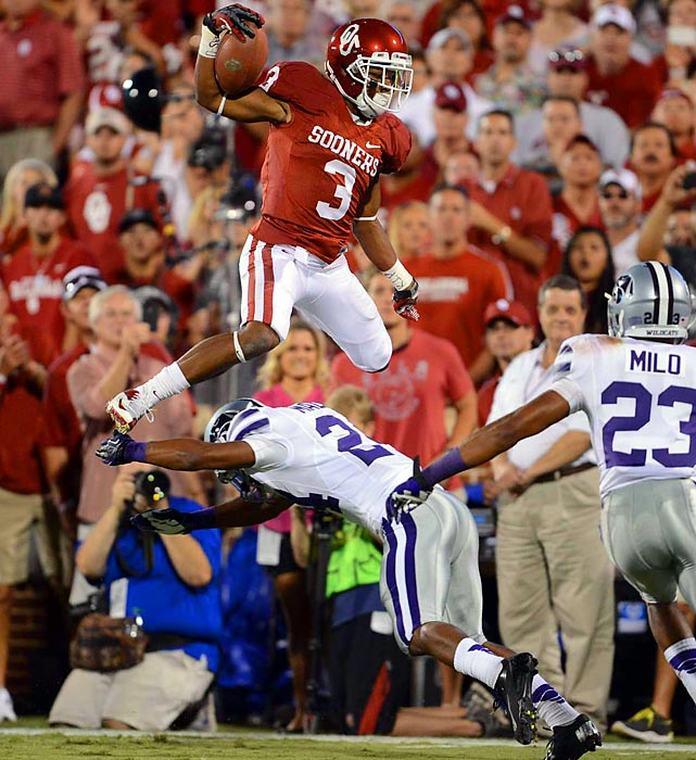 Oklahoma wide reciever Sterling Shepard leaps over Kansas State defensive back Nigel Malone for a first down deep in the red zone in the second quarter.