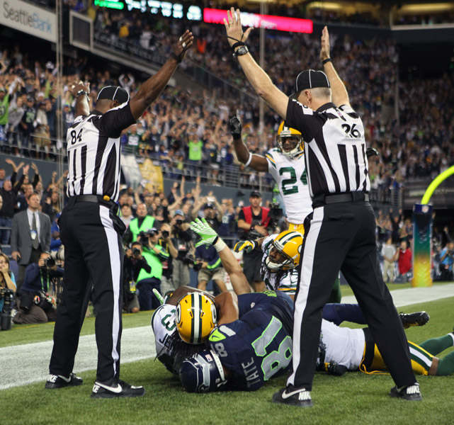 In what might have been the replacement referees' most controversial call to date, Seahawks wide receiver Golden Tate was ruled to have caught a game-winning touchdown as time expired despite what appeared to be an interception by Packers safety M.D. Jennings. One referee (left) ruled the pass an interception, while the other overruled and declared the desperation pass from Russell Wilson a touchdown.