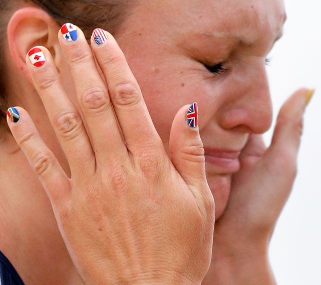 Painted fingernails decorate the hands of Germany's Lena Schoneborn as she comforts Margaux Isaksen of the U.S. after Isaksen finished fourth in the women's modern pentathlon during the 2012 Olympics.