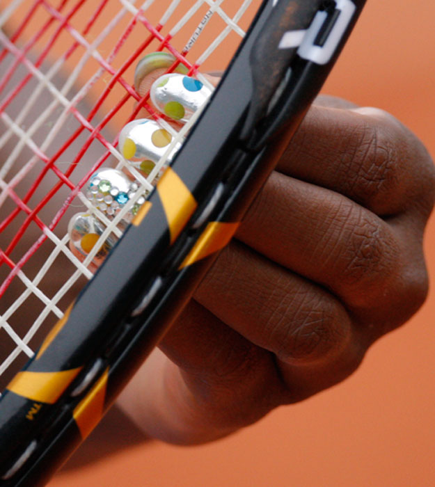 Never one to shy away from a bold fashion choice, Serena Williams shows off her nails while fixing her strings during the 2010 French Open.