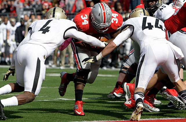 Ohio State's unbeaten season is still alive -- but just barely. The Buckeyes trailed Purdue by eight points with less than a minute remaining in regulation when quarterback Kenny Guiton, who took over for injured star Braxton Miller, pioneered a 61-yard touchdown and converted the ensuing two-point try to send the game to overtime. After Carlos Hyde (pictured) scored from one yard out to take the lead, Ohio State's defense shut down the Boilermakers to escape with their perfect record intact.