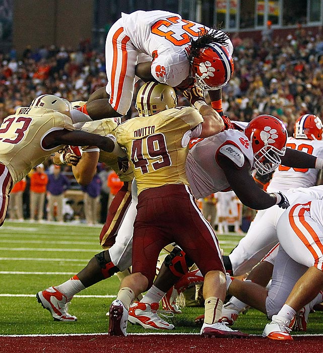 Clemson's Andre Ellington dives over Boston College's Steele Divitto to score a touchdown in the second half during Clemson's win on the road.