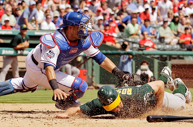 The A's Adam Rosales scores under the attempted tag by Rangers' catcher Geovany Soto during the third inning of the Rangers' 9-7 win.