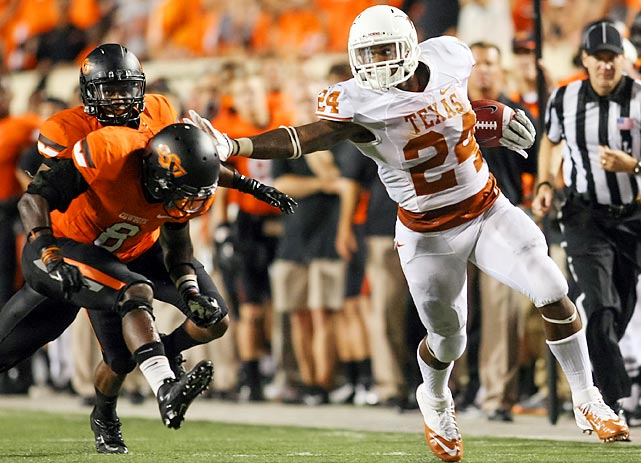 Texas running back Joe Bergeron (24) stiff arms Oklahoma State's Ashton Lampkin (6) during Texas's 41-36 win over the Cowboys.