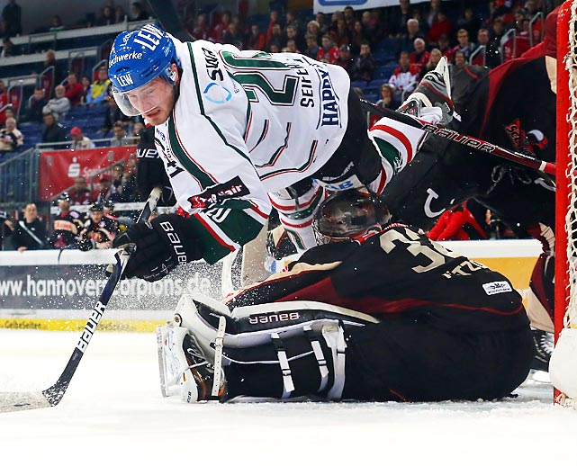 Hannover goaltender Dimitri Paetzold stops Augsburg's Patrick Seifert in front of the net during a DEL match.
