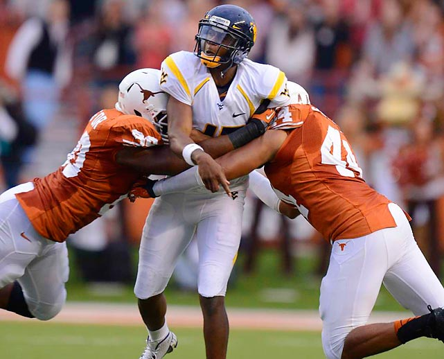 West Virginia quarterback Geno Smith gets crunched by Texas defenders Alex Okafor and Jackson Jeffcoat (44) during the Mountaineers' 48-45 victory over the Longhorns.