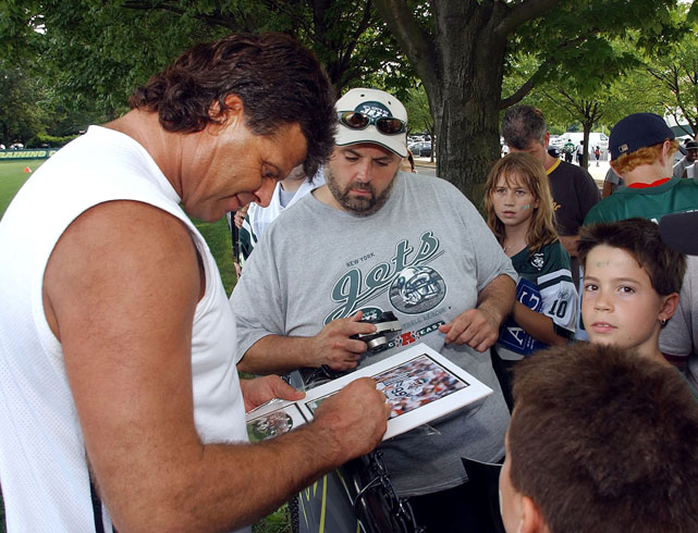Gastineau signs autographs while visting Jets training camp in Aug. 2004.
