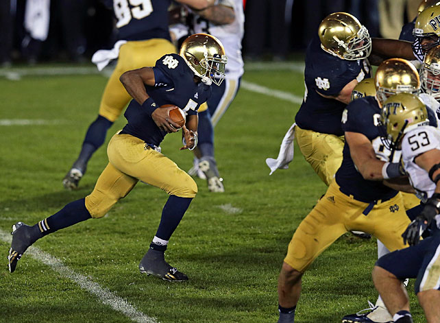 Notre Dame survives. That was the story from South Bend Saturday, as the Irish weathered a ferocious upset bid from Pitt to keep their surprising national title hopes alive. Down 20-6 in the fourth quarter, Everett Golson (pictured) orchestrated two scoring drives, the latter culminating in a five-yard touchdown pass to Theo Riddick. But the drama didn't end in overtime. Pitt kicker Kevin Harper missed a potential game-winning field goal, and Golson clinched the win with a dive into the end zone from one yard out. Panthers running back Ray Graham rushed for 174 yards and a score.
