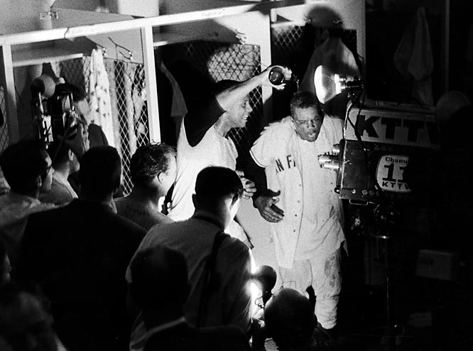 A teammate pours champagne over the head of Willie Mays in the locker room, to the delight of the assembled news media.