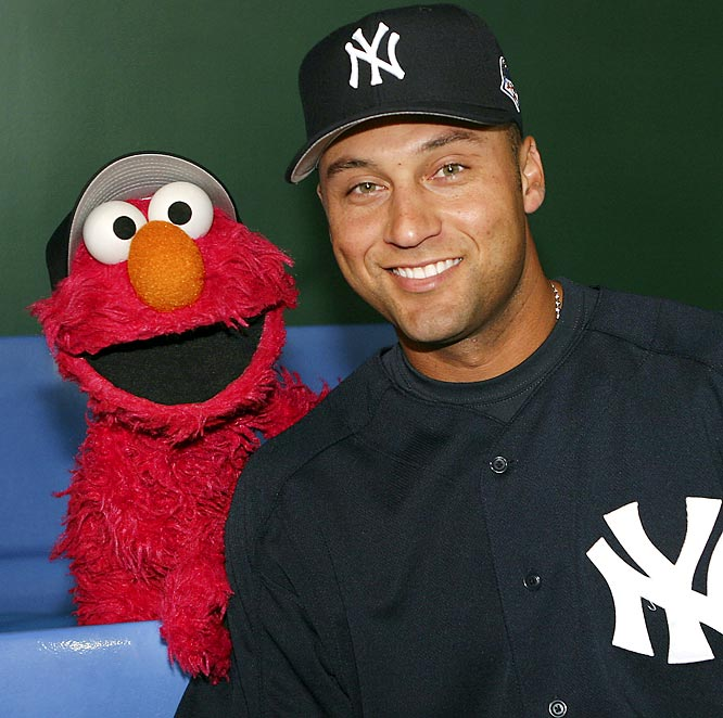 "Jeter grabs a hug with Sesame Street's ""Elmo"" during the Yankees 2004 trip to Japan."