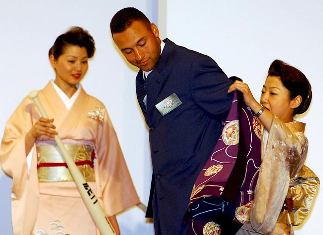 "Japanese women clad in a traditional kimono dress assists Jeter as he puts on a ""happi"" coat during a welcome reception for the Yankees and Devil Rays at a Tokyo hotel in March 2004."