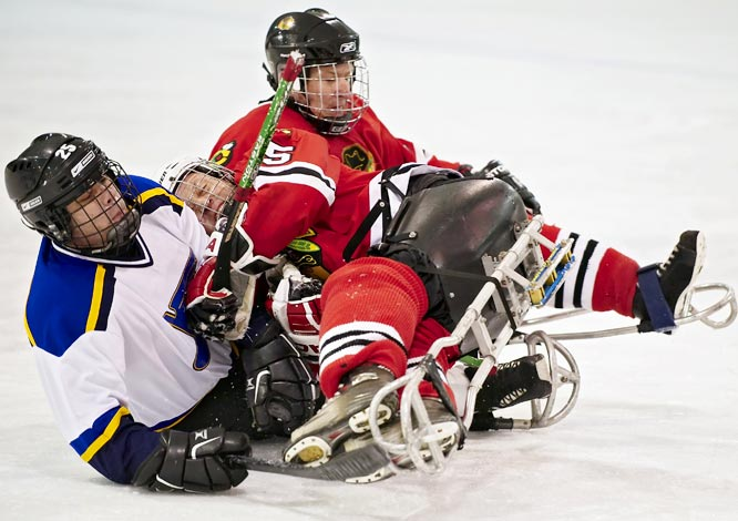 Sled hockey was designed to allow participants who have a physical disability to play the game of ice hockey, including veterans from the Iraq and Afghanistan wars.  The players consist of individuals who have sustained spinal cord injuries, amputations, spina bifida etc....   This game requires players to sit in a sled that has blades on the frame and allows the puck to pass underneath.  Players also have two shortened sticks that they use to not only push themselves along the ice, but it also allows them the ability to pass and shoot the puck as well.