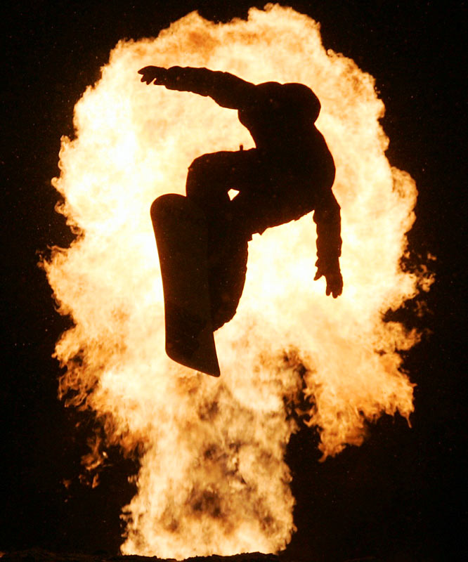 """This snowboarding event was run after dark on a poorly lit mountain slope in Killington, Vt. Normally, this light would be the kiss of death for taking pictures, but I was saved by the wonderful ball of fire that set off each time a snowboarder went over the jump. The hard part was figuring out which way the skier would go. A bit of luck helped. This one took a line straight in front of the fire, which showed him to be a snowboarder in mid-flight."""